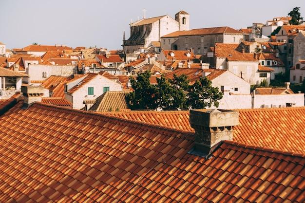 Eine nahaufnahme der dachziegel eines hauses vor dem hintergrund anderer häuser mit orangefarbenen dächern
