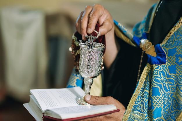 Eine nahaufnahme der hände des armenischen priesters, der zeremonie in der armenischen kirche tut