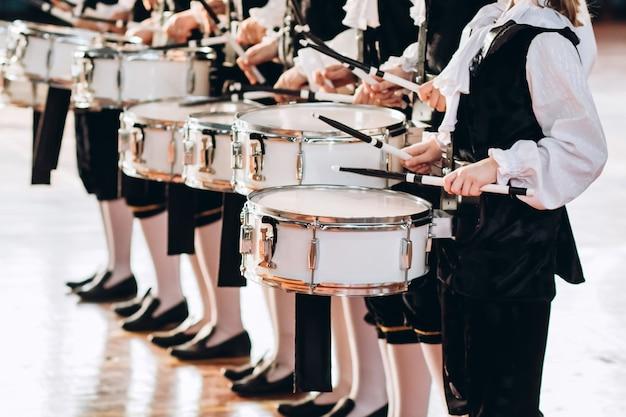 Eine nahaufnahme der hände eines schlagzeugers bei einer parade. kinderensemble in weißen hemden. weiße neue snaredrum, weiße sticks. das konzept einer militärparade und eines marsches.