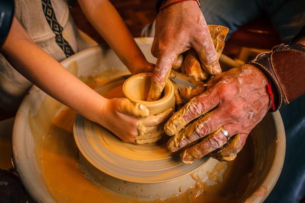 Eine nahaufnahme der hand eines männlichen töpfers, der seinen schüler unterrichtet