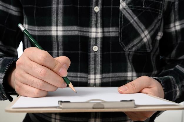 Eine nahaufnahme der hand eines mannes, die ein dokument mit einem klemmbrett unterzeichnet.