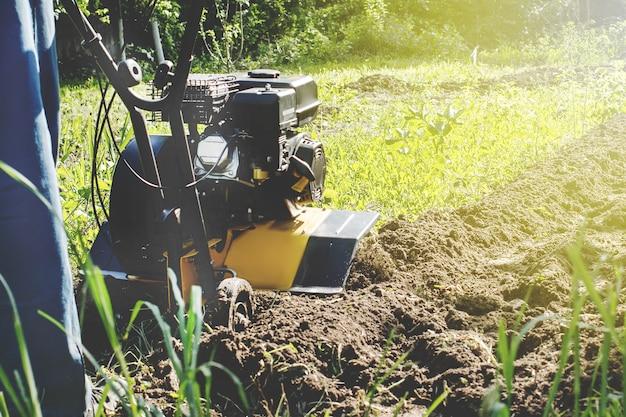 Eine nahaufnahme des motorgrubbers während des pflugprozesses im frühjahr gartenarbeitskonzept