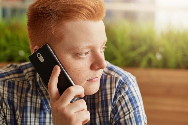 Eine nahaufnahme des stilvollen rothaarigen mannes mit sommersprossen und dunklen augen, die seitlich über grün sitzen und smartphone auf seinem ohr halten, das mit einigen kommuniziert