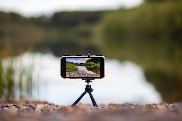 Eine nahaufnahme des telefons auf einem stativ nimmt ein video oder ein naturfoto auf. ein schöner see im wald mit wolken auf dem bildschirm des handys des fotografen.