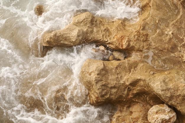 Eine nahaufnahme des türkisfarbenen wassers des mittelmeers und der starken wellen, die gegen die felsen an der küste schlagen. selektiver fokus