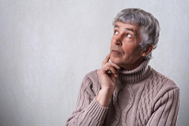 Eine nahaufnahme des verträumten älteren mannes, der seine hand unter dem kinn hält und beiseite schaut, mit nachdenklichem fernem ausdruck