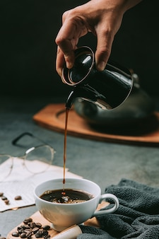 Eine nahaufnahme einer hand, die kaffeewasser in eine kaffeetasse gießt, internationales kaffeetagkonzept