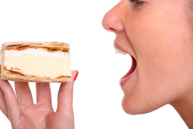 Eine nahaufnahme einer jungen frau, die einen windbeutel über weiß isst