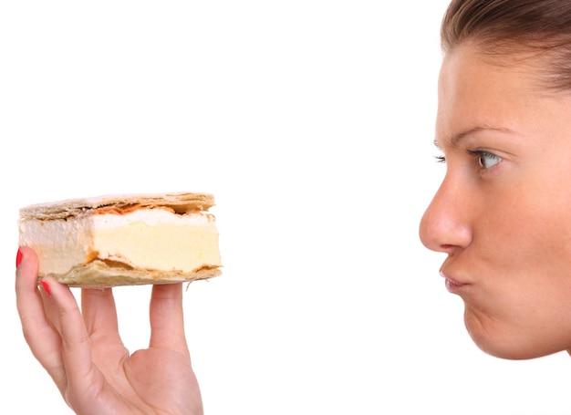 Eine nahaufnahme einer jungen frau, die versucht, der versuchung zu widerstehen, einen windbeutel über weiß zu essen?