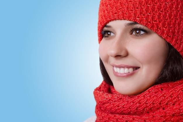 Eine nahaufnahme einer jungen frau mit braunen augen und einem schönen, angenehmen lächeln, die einen warmen hut mit schal trägt