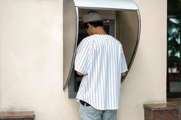 Eine nahaufnahme einer person, die geldautomaten verwendet, um bargeld von der bankkarte zu nehmen