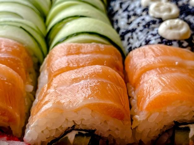 Eine nahaufnahme einer reihe von sushi-rollen. lieferung nach hause, japanische küche.