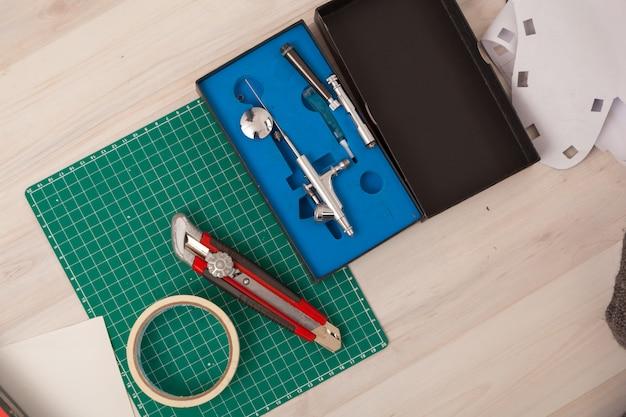 Eine nahaufnahme einer reihe von werkzeugen: ein papierschneidemesser, ein millimeterpapier.