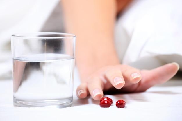 Eine nahaufnahme einer weiblichen hand, die nach einigen tabletten auf weißem hintergrund greift Premium Fotos