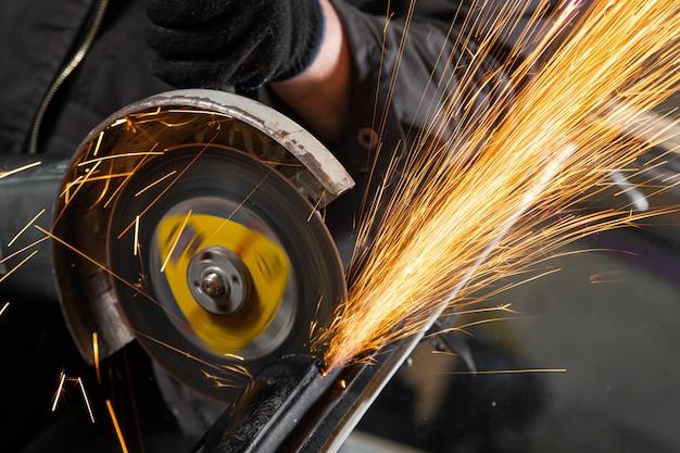 Eine nahaufnahme eines automechanikers, der einen metallschleifer verwendet, um einen autostummblock in einem schraubstock in einer autowerkstatt zu schneiden, helle blitze fliegen in verschiedene richtungen, in den wandwerkzeugen für eine autoreparatur