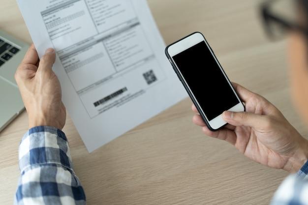 Eine nahaufnahme eines mannes, der ein mobiles smartphone verwendet, um den qr-code von einer rechnung auf einem dokument gegen eine gebühr zu scannen. das konzept der finanztechnologie, online-rückzahlung.