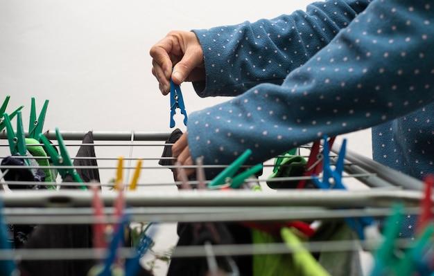 Eine nahaufnahme eines menschen, der seine frisch gewaschenen kleider mit hilfe der bunten kleiderschneider aufhängt