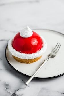 Eine nahaufnahme eines roten und weißen mousse-tartelette-desserts auf einem weißen teller