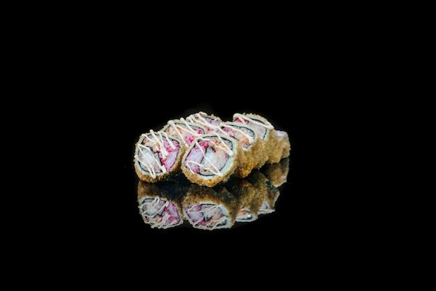 Eine nahaufnahme von gebratenen sushi-rollen des essens lokalisiert auf schwarzer reflexion