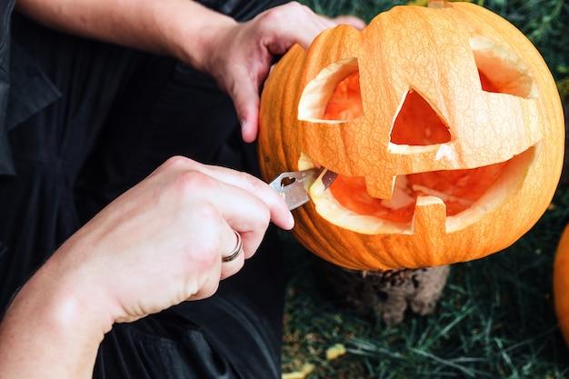 Eine nahaufnahme von mannhänden, die mit einem messer einen kürbis schneiden, während er eine kürbislaterne vorbereitet.
