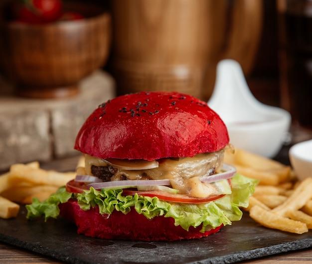 Eine nahaufnahme von rotem burger mit salat, zwiebel, geschmolzenem käse
