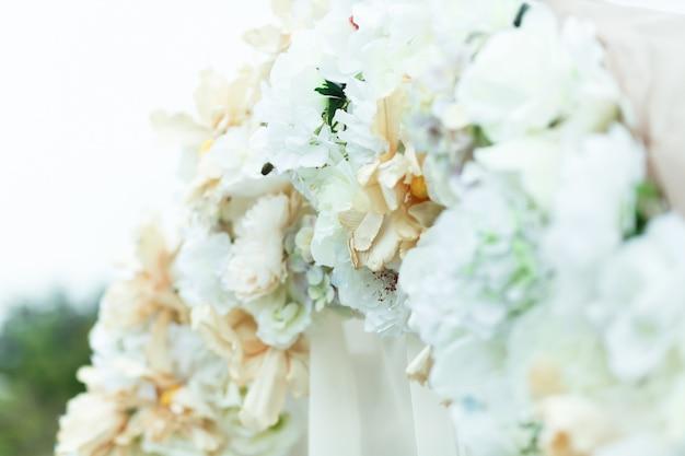 Eine nahaufnahme von weiß- und beigblumen auf dem hochzeitsaltar