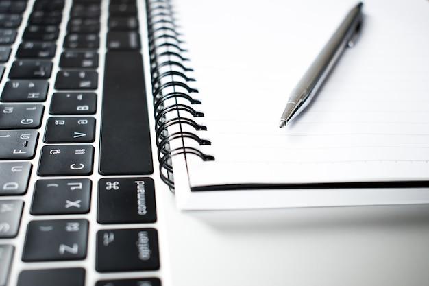 Eine nahe fotografie eines stiftes gelegt in ein notizbuch und in einen computer eines jungen geschäftsmannes.