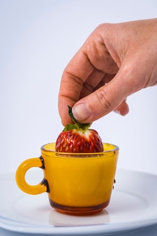 Eine nasse erdbeere in einer milchschale, die von einer frauenhand auf weiß gehalten wird