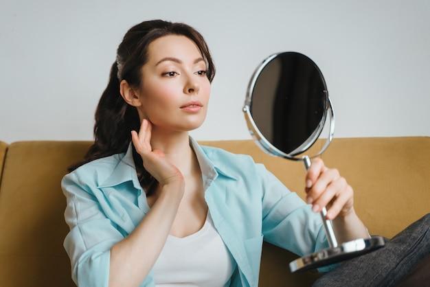 Eine natürliche frau mit guter haut hält ihre wangen und schaut in den spiegel spa kosmetik schönheit