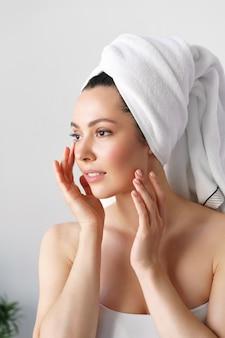 Eine natürliche frau mit guter haut hält ihre wangen und schaut in den spiegel. spa, kosmetologie, schönheit
