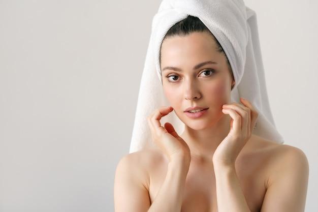 Eine natürliche frau mit guter haut hält ihre wangen und schaut in den spiegel. spa, kosmetologie, schönheit.