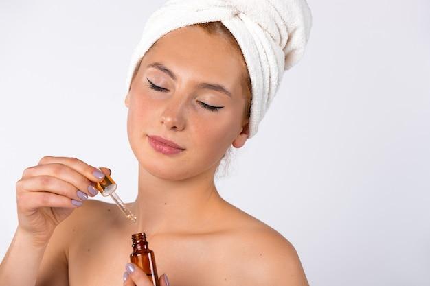 Eine natürliche frau ohne make-up mit einer pipette und anti-alter-serum in ihren händen naturkosmetik