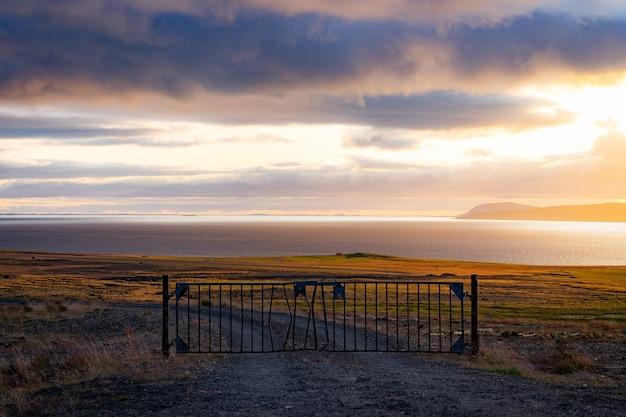 Eine neblige landschaft mit tor und dramatischer wolkenlandschaft während des sonnenuntergangs