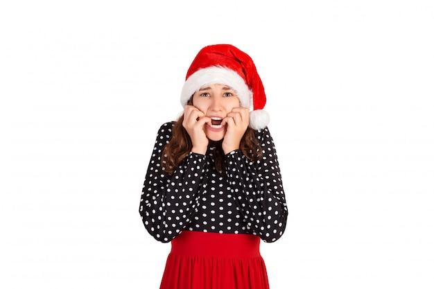Eine nervös verängstigte frau mit einem traurigen gesichtsausdruck und zusammengebissenen zähnen erfährt von einem tragischen ereignis. emotionales mädchen im weihnachtsmann-weihnachtshut lokalisiert auf weißem hintergrund. urlaub