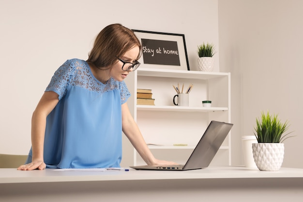 Eine nervöse junge geschäftsfrau, die im weißen büroraum steht