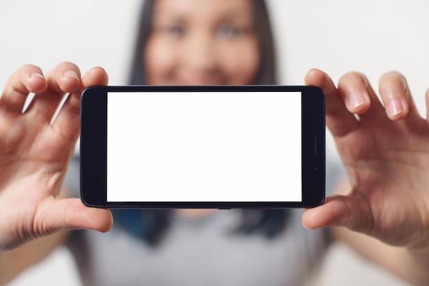 Eine nette frau, die ein smartphone mit einem leeren weißen bildschirm mit zwei händen horizontal hält und auf weißer wand lächelt