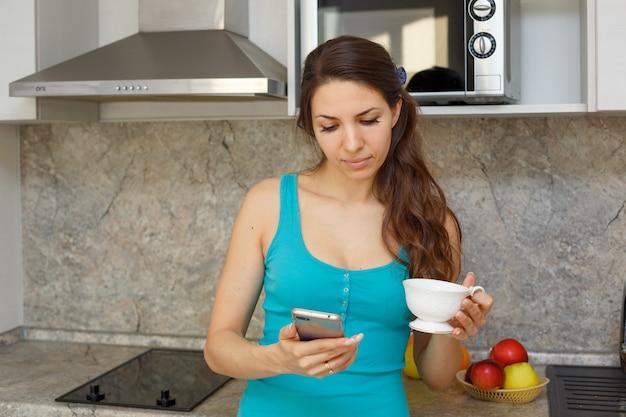 Eine nette frau in einem grünen t-shirt und dunklen haaren steht mit einem becher und einem telefon in der hand in der küche.