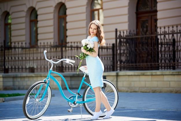 Eine nette frau mit pfingstrosen in den händen nahe einem blauen retro-fahrrad
