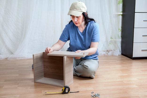 Eine neue kaukasische frau, die neue möbel auf dem boden selbst zusammenbaut.