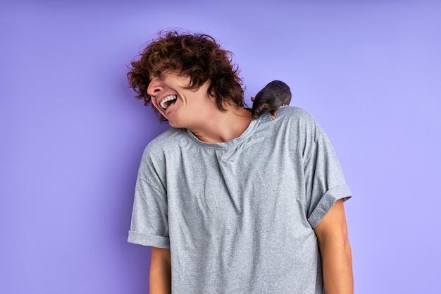 Eine neugierige graue ratte, die auf den schultern eines mannes kriecht, ein erschrockener und verängstigter kerl, steht unter schock