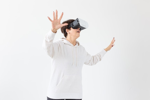 Eine nicht identifizierte frau mittleren alters in einem leichten pullover spielt ein 3d-spiel mit einer brille der virtuellen realität