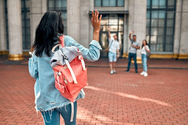 Eine niedliche afroamerikanische studentin mit einem rosa rucksack, der einer gruppe von studenten nahe dem campus winkt.