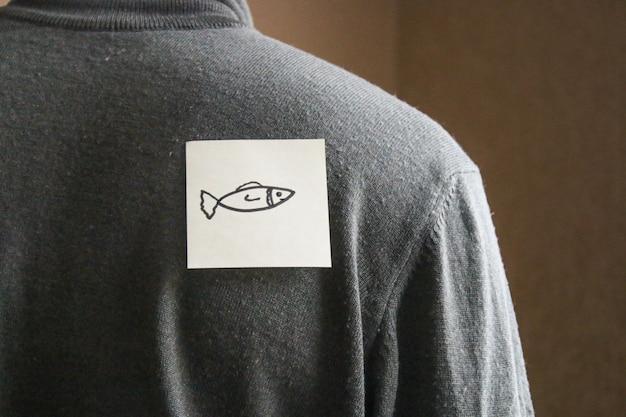 Eine notiz auf der rückseite eines jungen mannes mit einem komischen text. ein witz bis zum ersten april