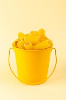 Eine nudel innerhalb des korbs der vorderansicht bildete rohen inneren gelben korb auf dem italienischen essen der sahnehintergrundmahlzeitspaghetti