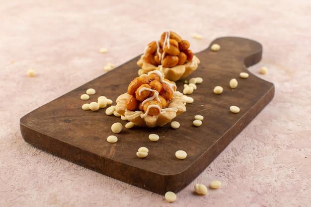 Eine nusskuchen von vorne sieht köstlich und klebrig auf dem hölzernen schreibtischkuchen