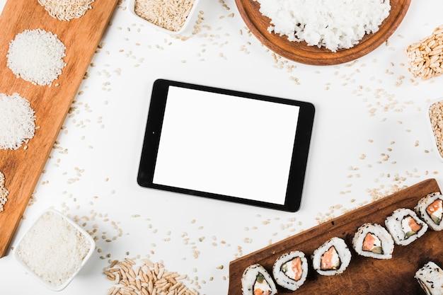 Eine obenliegende ansicht der digitalen tablette umgeben mit sushi und vielzahl des ungekochten reises