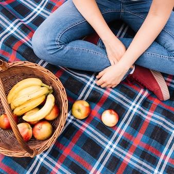 Eine obenliegende Ansicht der Frau sitzend auf Decke mit Obstkorb