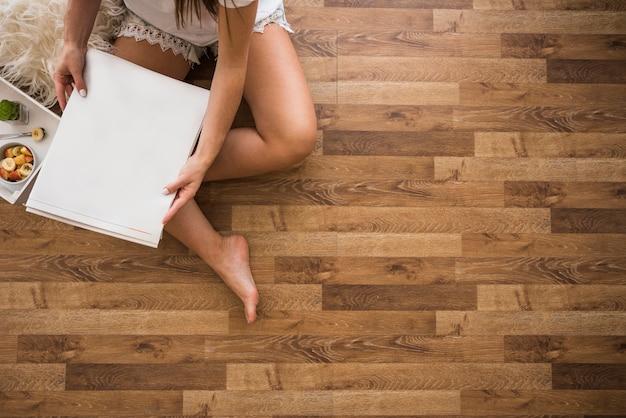 Eine obenliegende ansicht der frau sitzend auf dem massivholzboden, der weißes leeres papier hält