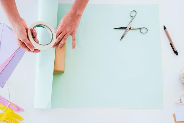Eine obenliegende ansicht der hand der frau das papier auf geschenkbox über dem weißen schreibtisch haftend