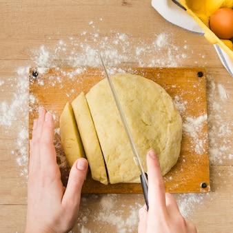 Eine obenliegende ansicht der hand der frau den teig für das zubereiten der italienischen gnocchiteigwaren auf holztisch schneiden